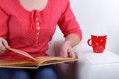 Mujer sentada en el sofá, leyendo el libro y beber café o té, primer plano — Foto de Stock