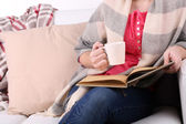 Femme assise sur le canapé, lecture de livre et la boisson café ou thé, gros plan — Photo