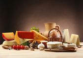 Tasty dairy products on wooden table, on dark background — Stock Photo