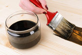 Applying protective varnish to wooden board close-up — Stockfoto