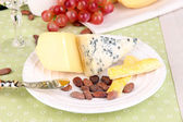 Assorted cheese plate, cocoa beans and grape on pink close-up — Stock Photo