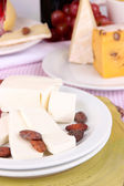 Assorted cheese plate on pink tablecloth background, close-up — Stock Photo