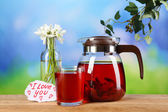 Tasty herbal tea and bouquet on table — Stock Photo