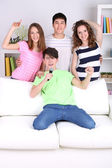 Group of young friends singing karaoke at home — Stockfoto