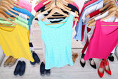 Different clothes on hangers and shoes on light background — Foto de Stock