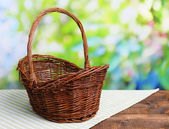 Empty wicker basket on wooden table, on bright background — Stock Photo