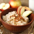 Tasty oatmeal with nuts and apples on wooden table — Stock Photo #44192859