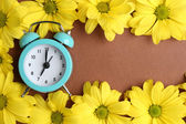 Alarm clock and beautiful flowers on brown background — Stock Photo
