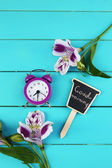 Alarm clock and beautiful flowers on blue wooden background — Stock Photo