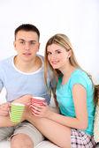 Milující pár sedící s cups na pohovku, na domácí interiér pozadí — Stock fotografie