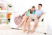 Loving couple sitting with laptop on sofa, on home interior background — Stock Photo