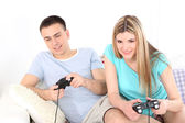 Couple playing video games on home interior background — Stock Photo