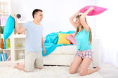 Couple fighting together with pillows on home interior background — Stock Photo