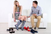 Loving couple choose new shoes, on light background — Foto Stock