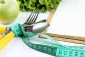 Cutlery tied with measuring tape and book with greens close up — Stock Photo