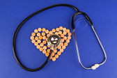 Heart of pills and stethoscope on blue background — Stock Photo