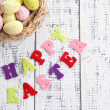 Easter eggs in nest and sign on color wooden background — Stock Photo