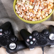 Black game controllers and bowl with pop corn on color plaid background — Stock Photo #44408445