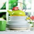 Stack of colorful ceramic dishes and flowers, on wooden table, on light background — Stock Photo #44408967