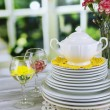Stack of colorful ceramic dishes and flowers, on wooden table, on light background — Stock Photo #44408985
