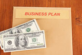 "Paper folder with the words ""business plan"" on wooden background close-up — Stock Photo"