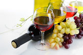 Bottle and glasses of wine and ripe grapes isolated on white — Foto de Stock