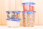 Filled plastic containers on wooden background — Stock Photo