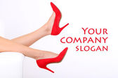 Beautiful female legs in red shoes isolated on white — Stock Photo