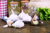 Composition with garlic press, fresh garlic and glass jars with spices on wooden background — ストック写真