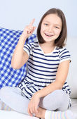 Beautiful little girl sitting on sofa, on home interior background — Stock Photo