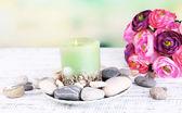 Composizione con pietre spa, candela e fiori su un tavolo in legno di colore, su sfondo chiaro — Foto Stock