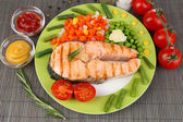 Tasty grilled salmon with vegetables, on bamboo mat — Stock Photo