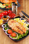 Tasty grilled salmon with lemon and vegetables, on wooden table — Stock Photo