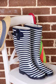 Pair of colorful gumboots on chair on color wall background — Stock Photo