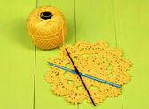 Yellow yarn for knitting with napkin and spokes on wooden table close-up — Stock Photo