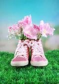 Krásný polokecky s květinami uvnitř na zelené trávě, na světlé pozadí — Stock fotografie