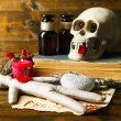Conceptual photo of love magic. Composition with skull, voodoo doll, dried herbs and candle on dark wooden background — Stockfoto #44415665