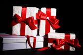 красивые подарки с красной ленты, на темном фоне — Стоковое фото
