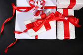Beautiful gifts with red ribbons, on dark background — Stock Photo