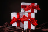 Beautiful gifts with red ribbons on silk, on dark background — Photo