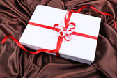 Beautiful gift with red ribbons on silk background — Stockfoto