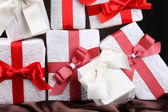 Beautiful gifts with red ribbons, close up — Stockfoto