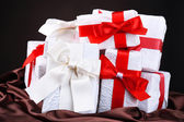 Beautiful gifts with red ribbons on silk, on dark background — Stockfoto