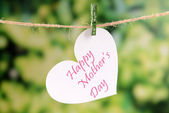 Happy Mothers Day message written on paper heart with flowers on bright background — Stock Photo