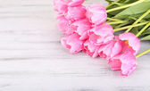 Beautiful pink tulips on wooden table — Stock Photo