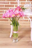 Beautiful pink tulips on brick wall background — Stockfoto