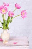 Beautiful pink tulips on grey wall background — Stockfoto
