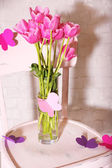 Composition with bouquet of tulips in vase, on chair, on wall background — Stock Photo
