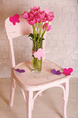 Composition with bouquet of tulips in vase, on chair, on wall background — Stockfoto