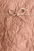String tied in  bow on brown paper packaging close-up — Stock Photo